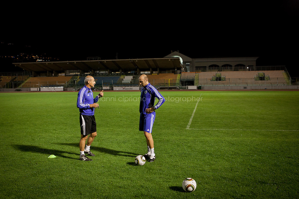 SERRAVALLE, SAN MARNO - 3 OCTOBER 2011:  Fabio Bollini (right), 28, listens the advices of athletic trainer Stefano Berti (left) at the Olympic Stadium before the upcoming and last Euro 2012 qualification game against Moldova on October 11, in San Marino on October 3, 2011. Fabio Bollini works at Traslocasa, the moving company he owns with his brother. The San Marino national football team is the last team in the FIFA  World Ranking (position 203). San Marino, whose population reaches 30,000 people, has never won a game since the team was founded in 1988. They have only ever won one game, beating Liechtenstein 1&ndash;0 in a friendly match on 28 April 2004. The Republic of San Marino, an enclave surronded by Italy situated on the eastern side of the Apennine Moutanins, is the oldest consitutional republic of the world<br /> <br /> <br /> ph. Gianni Cipriano