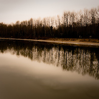 A winter photo of a river bank with a row of trees at an angle, reflecting in the water.