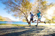 Two runners around a fall lake in New Zealand running with motion blur as they run.