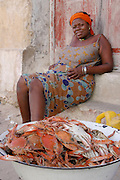 An African lady selling her caught crab on the island of Ilha De Mocambique (Mozambique Island), Northern Mozambique, Africa.