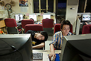 Fatigue takes its toll on dedicated extreme gamer, Xu Zhipeng (left), who plays online games day and night at Ming Wang Internet cafe in Shanghai, China. (From the book What I Eat: Around the World in 80 Diets.)  he caloric value of his day's worth of food in June was 1600 kcals. He is 23 years of age; 6 feet, 2 inches tall and 157 pounds.  He lives at his computer station, day and night, sleeping there when he's tired and showering once a week at a friend's apartment. His longest continuous game lasted three days and three nights. When he tires of gaming at the café he reads fantasy books. ?It's nice to rest your eyes on a book,? he says, even though he's reading it online. China has more than 300 million Internet users?a number close to the entire population of the United States. MODEL RELEASED.