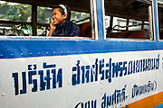 Mar 18, 2009 -- BANGKOK, THAILAND: A passenger on a municipal bus in Bangkok, Thailand, chats on her cell phone while the bus is stuck in traffic.  Photo by Jack Kurtz