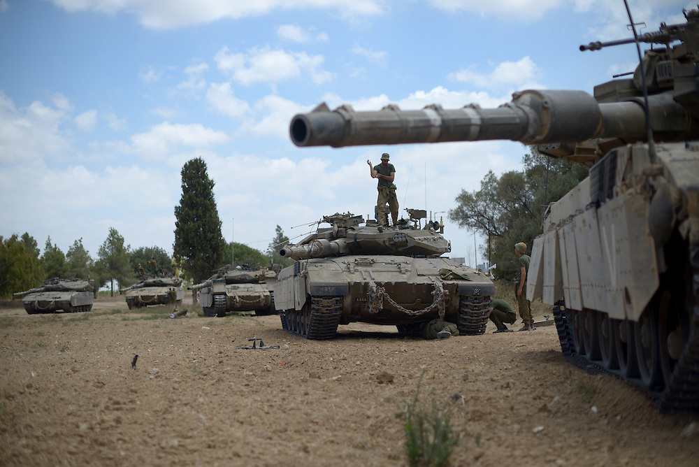UNSPECIFIED, ISRAEL - JULY 17, 2014: An Israeli soldier stands atop a Merkava tank, at an army deployment area near Israel's border with the Gaza Strip, on July 17, 2014. Photo by Gili Yaari.