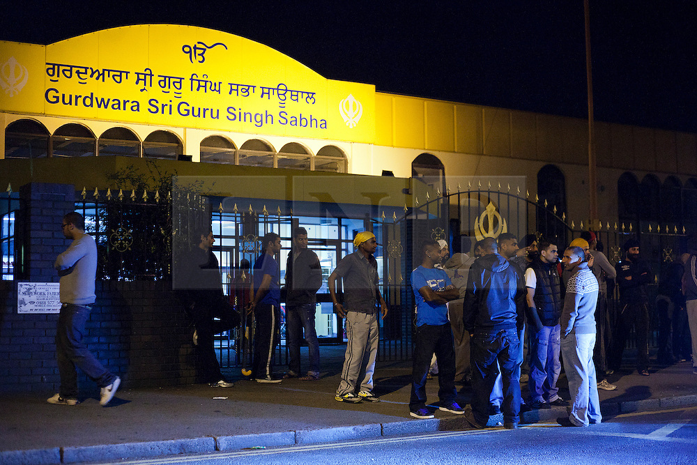 © Licensed to London News Pictures. 10/08/2011. LONDON, UK. Sikh males stand outside Gurdwara Sri Guru Singh Sabha, part of the largest Sikh temple in Europe, as they keep watch for possible trouble. Organised, and coordinating with police, members of Southall's Sikh community come out in force to prevent any rioting from taking place in the area. The vigilante action took place as a fourth night of riots and looting were expected to take place in London. Photo credit: Matt Cetti-Roberts/LNP