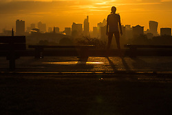 Primrose Hill, London, October 28th 2016. A woman admires the sunrise over the City's skyline as a new day breaks over London.