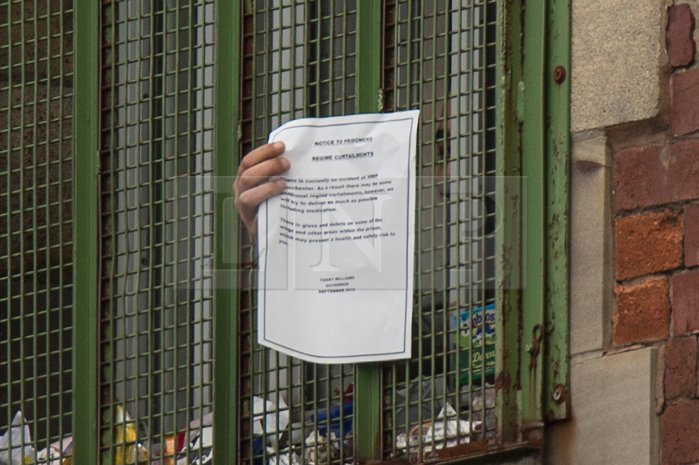 "© Licensed to London News Pictures . 14/09/2015. Manchester, UK. A prisoner holds a note through his cell window , delivered from prison authorities at HMP Manchester , describing "" regime curtailments "" due to the ongoing rooftop protest by Stuart Horner , who is demonstrating against prison conditions . Photo credit : Joel Goodman/LNP"