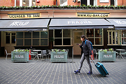 © Licensed to London News Pictures. 05/02/2020. London, UK. A woman with a suitcase walks past a Chinese restaurant in Chinatown with no customers eating outside,  following the outbreak of Coronavirus in Wuhan, China. At least 427 people have died from the virus and there have been over 20,000 confirmed cases, most of them in China. Photo credit: Dinendra Haria/LNP