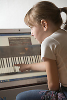Child leans keywboard on computer with touch screen technology
