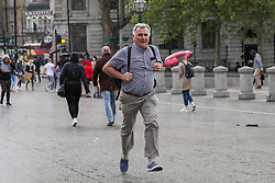 © Licensed to London News Pictures. 04/05/2019. London, UK. A man runs for shelter as it starts to rain suddenly in Trafalgar Square. Photo credit: Dinendra Haria/LNP