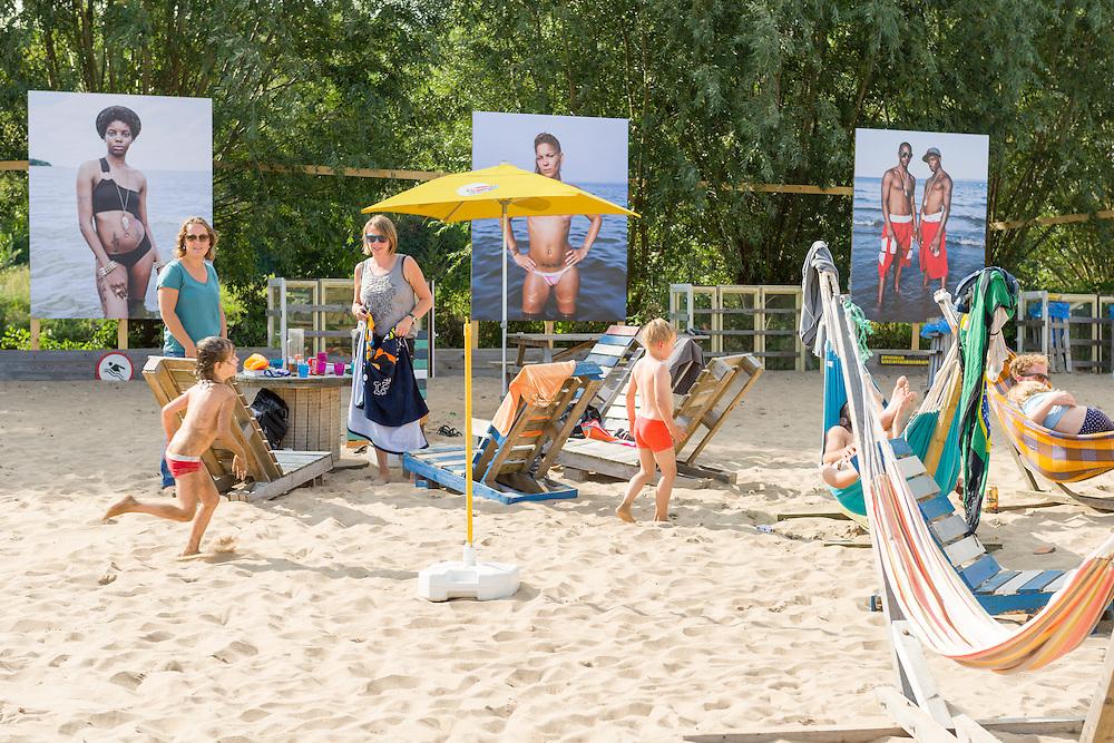 Nederland, Breda, 20140912.<br /> Belcrum Beach, het Bredase strand, heeft een buitententoonstelling van Breda Photo. Tijdens het festival zijn foto's te zien van An-Sofie Kesteleyn, Wayne Lawrence en Ed Templeton. <br /> Mensen zitten in de zon op het strand. Kinderen spelen. <br /> BredaPhoto is een internationaal fotofestival dat sinds 2003 iedere twee jaar plaatsvindt in het stadscentrum van Breda. Zeven weken lang biedt het festival een gevarieerd programma. Gevestigde fotografen uit binnen- en buitenland staan er naast jong talent. Dit festival is het werk van 54 fotografen te zien.<br /> Met het festivalthema Songs from the Heart duikt BredaPhoto 2014 in de 21ste-eeuwse romantiek.<br /> <br /> Netherlands, Breda, 20140912.<br /> Belcrum Beach, Breda Beach has an outdoor exhibition of Breda Photo. During the festival, works of An-Sofie Kesteleyn, Wayne Lawrence and Ed Templeton can be seen here..<br /> People sitting in the sun on the beach. Children play.<br /> <br /> Chass&eacute; Park transformed back to the extensive outdoor exhibition Chasse XXL: day and night freely accessible, with photos in large format<br /> BredaPhoto international Photo festival takes place for the sixth time in the city center of Breda. The theme of the sixth edition of BredaPhoto international photo festival is Songs from the Heart. For seven weeks, Breda is all about photography with exhibitions of 54 photographers and dozens of lectures, book presentations and activities for all ages.<br /> 11 sep - 26 okt 2014<br /> With this theme, BredaPhoto 2014 dives into 21st-century Romanticism.