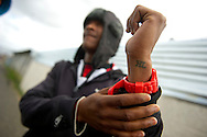 MANENBERG, SOUTH AFRICA - SEPTEMBER 14: A young man shows his tattoo for the 'Hard Livings' gang on September 14, 2013 in Manenberg, a township of Cape Town, South Africa. 'This is my first and last tattoo,' he says. The 'Americans' and the 'Hard Livings' are two of the larger gangs controlling turf in Manenberg. In August, 16 schools were closed in the area due to increasing gang violence. An uncertain peace has been brokered between the gangs to help the community resume their daily lives. Photo by Ann Hermes/The Christian Science Monitor