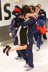 © Licensed to London News Pictures. 25/02/2014. London, UK. Men's Curling Silver medalist David Murdoch is greeted by his wife, Stephanie as he arrives at Heathrow Airport in London on 24th February 2014. Photo credit : Vickie Flores/LNP