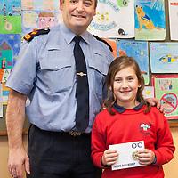 Ciara Ní Seasán from Clarecastle NS, a winner in the recent Ennis Garda Síochána Crime Prevention Art Competition receiving her medal from Superintendant Derek Smart