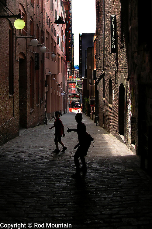 Two young boys stop and turn to look back as they make their way down Post Alley in Seattle, Washington. <br />