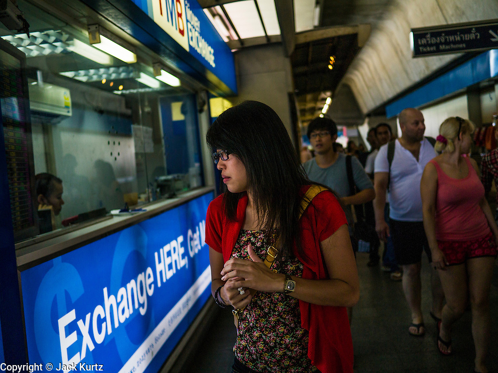 22 APRIL 2013 - BANGKOK, THAILAND:    A woman walks buy a TMB currency exchange kiosk in Bangkok. The Thai Baht has gained markedly against the US Dollar, the Euro and Pound Sterling in recent months. On Monday, the Baht was trading at 28.57 Baht to 1 US Dollar on Apr. 22. The strengthening Baht means imported goods are cheaper in Thailand, but Thai exports cost more in other countries. It also means tourists and expats who live in Thailand have less money to spend as their currencies buy fewer Baht. The baht has risen 5 percent against the dollar this year to its highest level since before the Asian financial crisis in 1997. The Federation of Thai Industries, which has led calls for the authorities to act to lower the baht, said the rise in the past two weeks had been too rapid and its members were finding it hard to cope with the volatility because as the Baht appreciates their exports become more expensive. Thailand is among the world's leading exporters of rice, chicken, pork, electrical components, cars and is the leading exporter of canned tuna. PHOTO BY JACK KURTZ