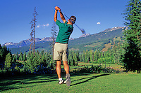 A male golfer tees off the 16th hole at the Whistler Golf Course on a summer day, Whistler, BC Canada.