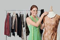 Portrait of beautiful female fashion designer adjusting cloth on tailor's dummy