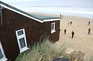 HOUSES THAT WERE PARTLY SWEPT INTO THE SEA AFTER ONE OF THE BIGGEST TIDAL SURGES SINCE 1953 HIT THE TOWN OF HEMSBY IN NORFOLK.7.12.13.PIX STEVE BUTLER 07970 430606