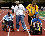 Zachary Grow, 18, assisted by his father Von, race against Joseph Roads and his son Dan, age 8, in the 25 meter Wheelchair Race last Saturday at James Logan High School, in Union City, for the 2003 Track & Field Qualifier of the Special Olympics.