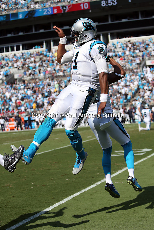 Carolina Panthers quarterback Cam Newton (1) leaps and celebrates with a teammate after throwing a 36 yard touchdown pass for a 24-10 fourth quarter lead during the 2015 NFL week 2 regular season football game against the Houston Texans on Sunday, Sept. 20, 2015 in Charlotte, N.C. The Panthers won the game 24-17. (©Paul Anthony Spinelli)