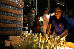 """Workers do quality control and ready bottles to hold Murree beer in Rawalpindi, Pakistan, Sept. 12, 2007. With a limited market in Islamic Pakistan, the company is looking for opportunities abroad. Soon the brewery's beer will be sold in Britain and India with the advertising slogan: """"Have a Murree with your curry."""" The almost 150 year old Murree Brewery is preparing to bring the Muslim world's first 20 year old single malt whisky to the market. However, they can only sell to non-Muslims, who comprise 3 percent of Pakistan's population."""