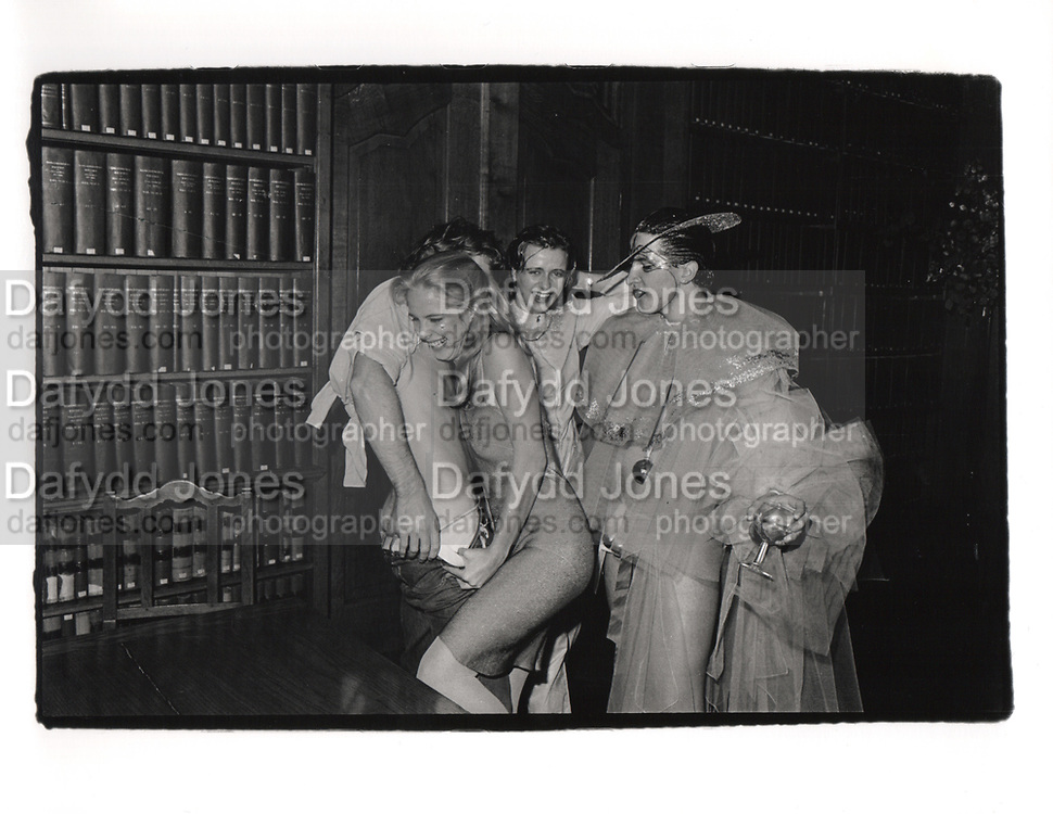 Paul Golding looks on as Katie removes trousers. Piers Gaveston drinks. Rhodes House. Oxford. 1980