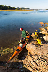 A man and a pair of kayaks next to the Essex River at the Cox Reservation in Essex, Massachusetts.
