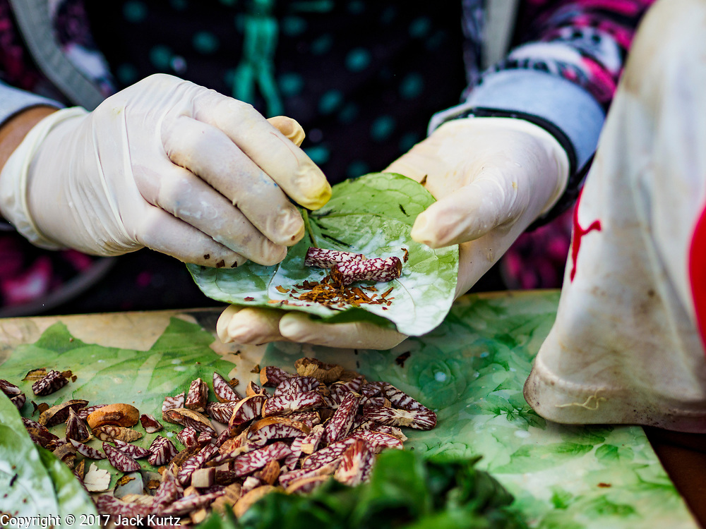 23 NOVEMBER 2017 - YANGON, MYANMAR: Making betel for sale to workers in the San Pya Fish Market. Betel is a mild stimulant rolled with betel nut, tobacco and other additives inside betel leaf. It used to chewed throughout Southeast Asia and India but health campaigns have seen betel use greatly reduced in most places besides Myanmar.  San Pya Fish Market is one of the largest fish markets in Yangon. It's a 24 hour market, but busiest early in the morning. Most of the fish in the market is wild caught but aquaculture is expanding in Myanmar and more farmed fresh water fish is being sold now than in the past.    PHOTO BY JACK KURTZ