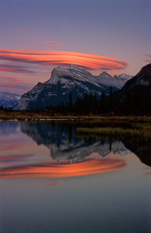 A lenticular cloud over Mt. Rundle is lit up by the dusk light and reflected off the Fisrt Vermillion Lake, on Banff National Park, in the Canadian Rockies
