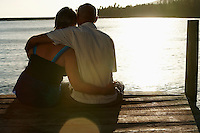 Senior couple sitting on edge of dock by lake back view.