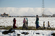 Bekaa Valley, LEBANON: A group of Syrian women and children walk along a path alongside an irrigation canal near their informal tented encampment days after a heavy snowfall paralyzed the region. Liam Maloney/Polaris Images