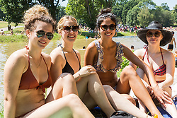 Friends Nadia Richards, 22, left, Elinor Doye, 22, second left, Megan Cha, 22 and Daisy Grierson, 22, rimghtejoy the hot weather at Beckenham Place. With temperatures soaring into the 30s hundreds take advantage of the hot weather and London's newest wild swimming lido at Beckenham Place in South East London. London, July 23 2019.