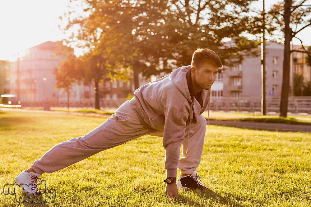 Young attractive man stretching in park