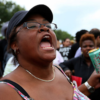 Demonstrators voice their opinions by singing and holding up signs in the protest area, prior to the trial of George Zimmerman at the Seminole County Courthouse, Saturday, July 13, 2013, in Sanford, Fla. Zimmerman had been charged for the 2012 shooting death of Trayvon Martin. Zimmerman was found not guilty by a jury of six women. (AP Photo/Alex Menendez)