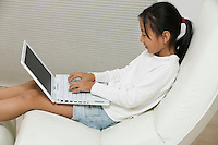 Young Girl in Chair Using Laptop