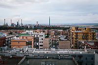 TARANTO, ITALY - 22 FEBRUARY 2018: The ILVA steel mill and the concrete flats of Tamburi, the adjacent working-class district, are seen here in Taranto, Italy, on February 22nd 2018.<br /> <br /> Taranto, a  formerly lovely town on the Ionian Sea has for the last several decades been dominated by the ILVA steel mill, the largest steel plant in Europe. It was built by the government in the 1960s as a means of delivering jobs to the economically depressed south, but has been implicated for a cancer as dioxin and mercury have seeped into local groundwater, tainting the food supply, while poisoning the bay and its once-lucrative mussels.