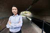Portrait of confident businesswoman standing arms crossed by canal