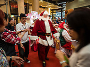 17 SEPTEMBER 2015 - BANGKOK, THAILAND:  A Santa Claus walks through the crowd at the World Santa Claus Congress in Bangkok. Twenty-six Santa Clauses from around the world are in Bangkok for the first World Santa Claus Congress. The World Santa Claus Congress has been an annual event in Denmark since 1957. This year's event, hosted by Snow Town, a theme park with a winter and snow theme, hosted the event. There were Santas from Japan, Hong Kong, the US, Canada, Germany, France and Denmark. They presented gifts to Thai children and judged a Santa pageant. Thailand, a Buddhist country, does not celebrate the religious aspects of Christmas, but Thais do celebrate the commercial aspects of the holiday.   PHOTO BY JACK KURTZ