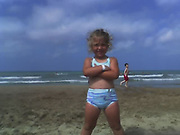 Child stands on the beach in her bathing suit.