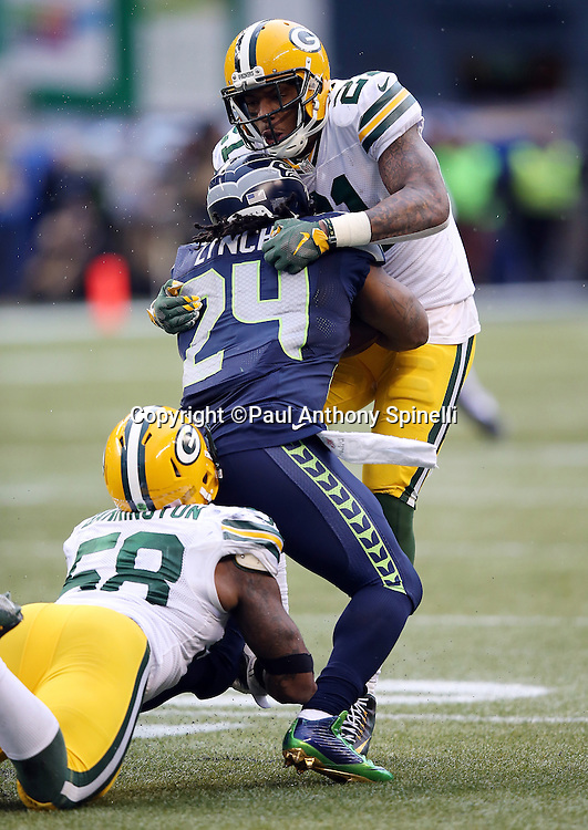 Seattle Seahawks running back Marshawn Lynch (24) gets gang tackled by Green Bay Packers inside linebacker Sam Barrington (58) and Green Bay Packers free safety Ha Ha Clinton-Dix (21) on a fourth quarter run for a first down during the NFL week 20 NFC Championship football game against the Green Bay Packers on Sunday, Jan. 18, 2015 in Seattle. The Seahawks won the game 28-22 in overtime. ©Paul Anthony Spinelli