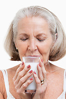 Senior woman drinking milk against white background