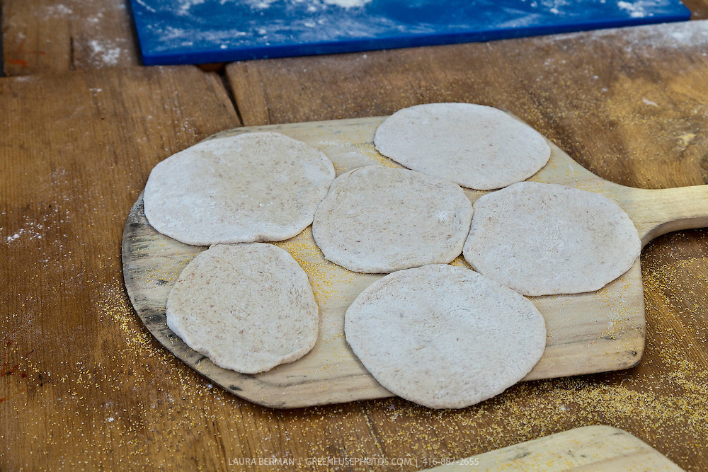 Cornmeal tortillas on a wooden oven paddle.