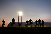 Steven St. John/Tribune..UNM football players wait on the sidelines under the lights as the sun begins to show during a scrimmage just after 6 a.m. on Tuesday morning, Aug. 21, 2007.