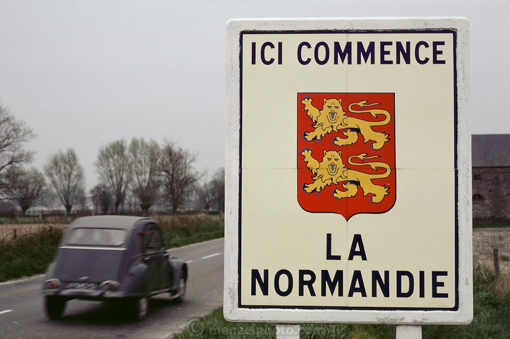 Deux cheveaux car, made by Citroen, on a road with a sign that says Normandy Starts Here. Normandy, France.