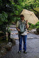 A Japanese man poses for the camera with his umbrella at the Golden Temple (Kinkaku-Ji) in Kyoto, Japan.