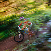 Heather Goodrich rides coastal singletrack on her mountain bike in late afternoon light near Anacortes, Washington.