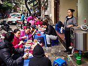 "22 DECEMBER 2017 - HANOI, VIETNAM: A woman watches her customers at her ""pho"" stand in the old quarter of Hanoi. Pho is Vietnamese beef noodle soup and is eaten at all times of the day. The old quarter is the heart of Hanoi, with narrow streets and lots of small shops but it's being ""gentrified"" because of tourism and some of the shops are being turned into hotels and cafes for tourists and wealthy Vietnamese.    PHOTO BY JACK KURTZ"