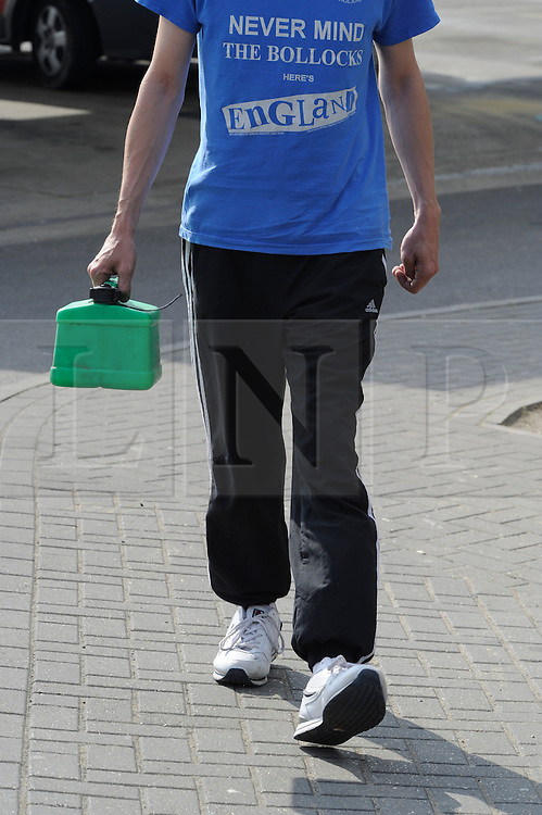 © Licensed to London News Pictures. 30/03/2012.Petrol Panic buying today 30.03.2012..Man filling a Jerry can at the BP garage on the A21 Lamberhurst Quarter, Kent..***warning  read mans t-shirt******** .Photo credit : Grant Falvey/LNP