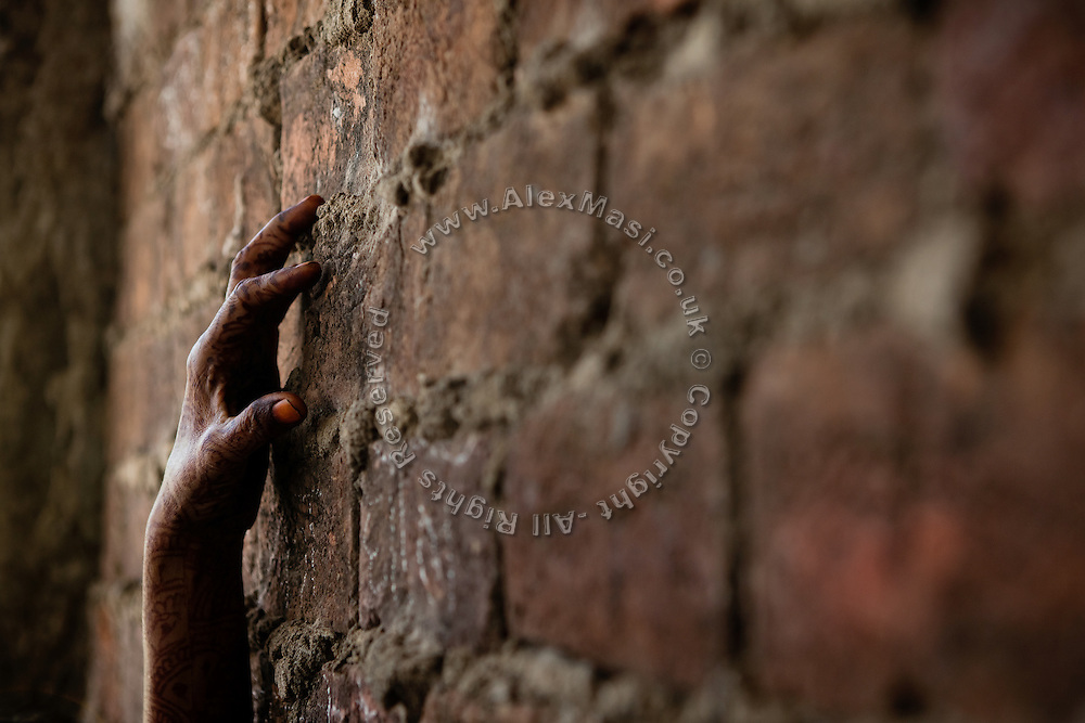 A woman's hand decorated with henna is touching the red brick wall, during a community meeting organised by the Bhopal Medical Appeal near the abandoned Union Carbide (now DOW Chemical) factory in Bhopal, Madhya Pradesh, India, site of the infamous 1984 gas disaster. Copyright: Alex Masi / Focus For Humanity