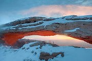 Sunrise lights up the bottom Mesa Arch on a snowy Winter morning, Canyonlands National Park, Utah